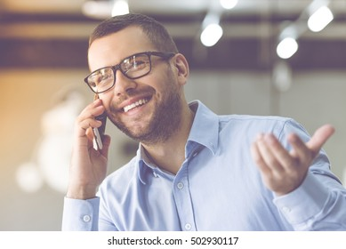 Handsome businessman in classic shirt and eyeglasses is talking on the mobile phone and smiling while working in office