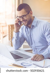 Handsome businessman in classic shirt and eyeglasses is using a laptop, talking on the mobile phone and smiling while working in office