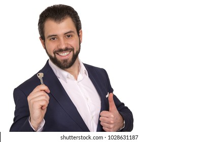Handsome businessman in classic suit smiling, holding keys, on white background