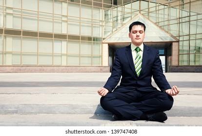 Handsome businessman doing yoga near building office