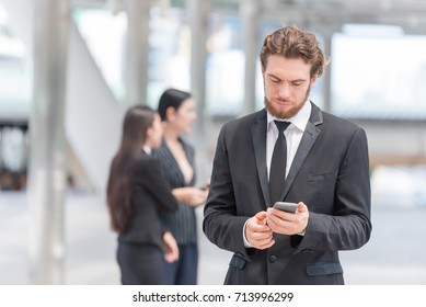Handsome businessman in downtown using smartphone finding location from map application searching to new group startup project.