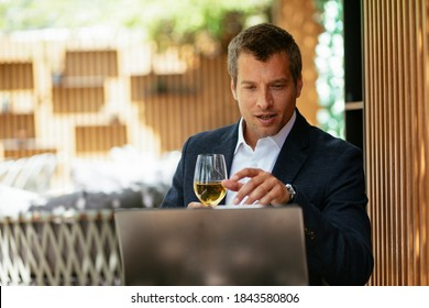 Handsome businessman dressed in the suit drinking wine. Businessman enjoying in the restaurant
