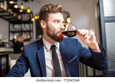 Handsome businessman dressed in the suit drinking red wine sitting at the restaurant