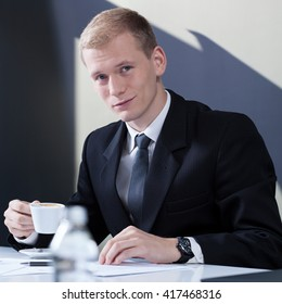 Handsome businessman drinking coffee in the office
