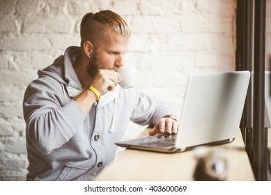 handsome businessman drinking coffee and working in coffee shop
