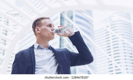 handsome businessman drinking fresh water from bottle on business district , business concept