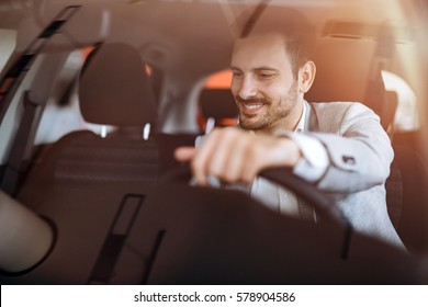 Handsome businessman driving car before buying