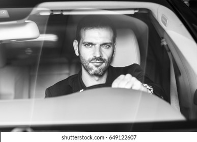 Handsome businessman driving a modern car.