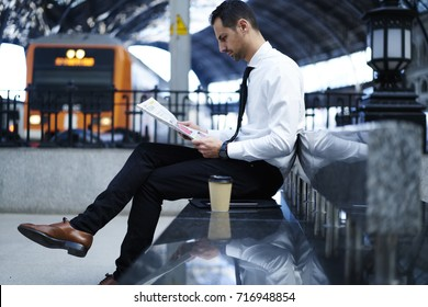 Handsome businessman in elegant formal outfit waiting for train in railway station reading financial news,pensive male manager spending time checking daily newspaper articles while staying on platform