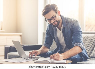 Handsome businessman in eyeglasses is making notes and smiling while working with a laptop at home