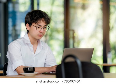 Handsome businessman in eyeglasses is using a computer working in office