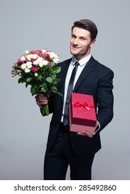 Handsome businessman with flowers and gift box standing over gray background