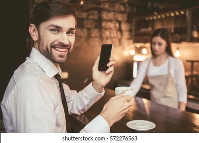 Handsome businessman in formal clothes is using a smartphone and smiling while sitting at the bar counter in cafe