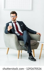 handsome businessman in formal wear sitting on armchair and using smartphone in office
