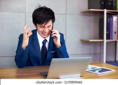 Handsome businessman gets angry so much when customer or employee is nagging him or telling some terrible things on phone. Attractive handsome guy gets frustrated, upset and unhappy at office