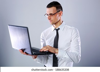 Handsome businessman in glasses using laptop over gray background