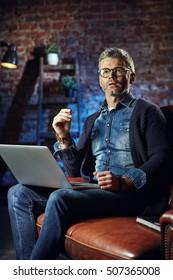 Handsome businessman with gray hair in loft studio