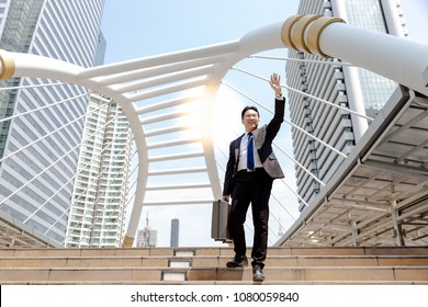A handsome businessman is greeting or saying hello his friend or customer. Charming guy feels happy when meet someone. He walk on steps at metropolis near office with copy space and city background