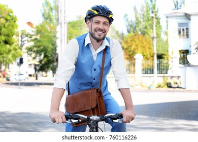 Handsome businessman in helmet riding bicycle outdoors
