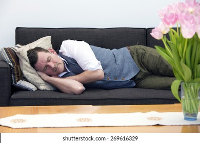 handsome businessman in his 50's sleeping on couch