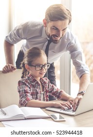 Handsome businessman and his cute little daughter are using a laptop and smiling while spending time together