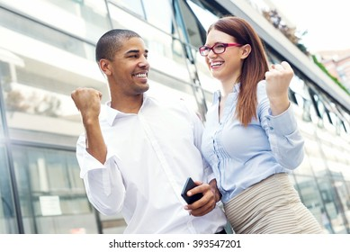 Handsome businessman and his partner holding their fists up, smiling and looking at each other.