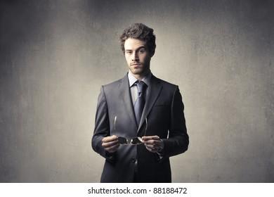 Handsome businessman holding eyeglasses
