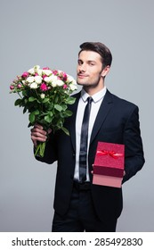 Handsome businessman holding flowers and gift box over gray background. Looking at camera