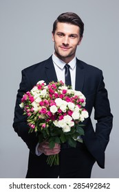 Handsome businessman holding flowers over gray background and looking at camera