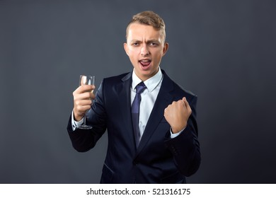 Handsome businessman holding a glass of champagne over gray background celebrating a victory, success