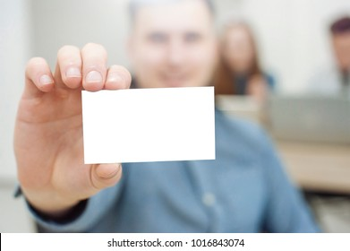 A handsome businessman holds a white business card in his hands, a white leaf. White letter card. Advertising News.Bigbord, Citylite. Company news. Schedule work at the firm in office