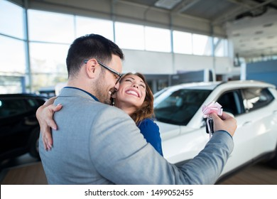 Handsome businessman husband holding keys and surprising his wife with a new car at vehicle dealership showroom. Happy people hugging and celebrating vehicle purchase.