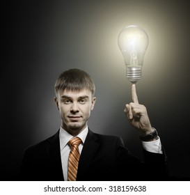 handsome businessman index finger point upwards with light bulb, on dark background