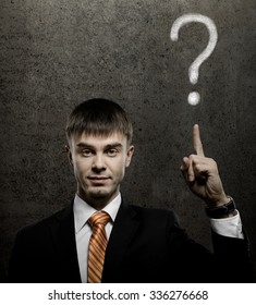 handsome businessman index finger point upwards on question, on dark grey background