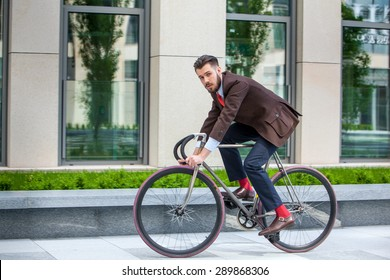 Handsome businessman in a jacket riding on his bicycle on city streets. The concept of the modern lifestyle of young men