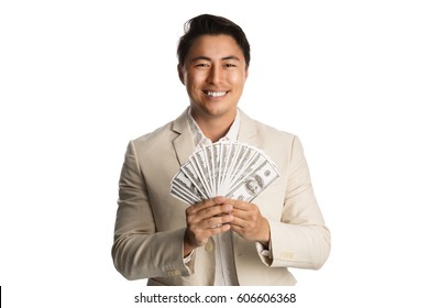 Handsome businessman in a khaki suit and shirt, standing against a white background holding a big fan of dollar bills with a big smile on his face.