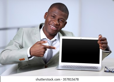 Handsome businessman with laptop, close up