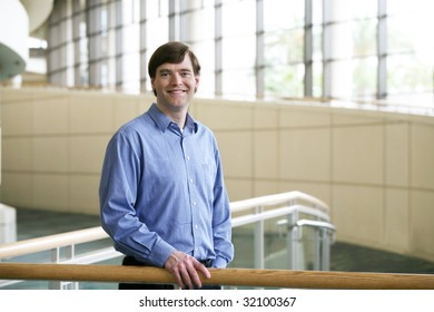 Handsome businessman leaning on railing in large office complex