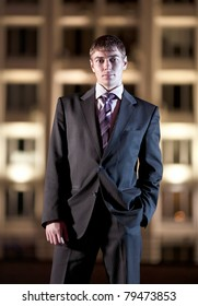 Handsome businessman and light building at night city in the background