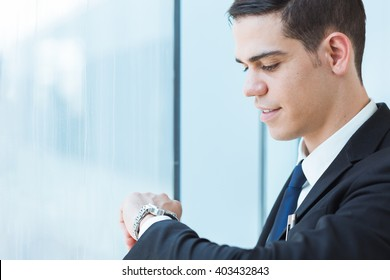 Handsome businessman looking at his watch.
