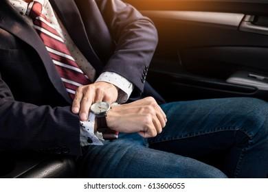 Handsome businessman looking on wrist watch in car