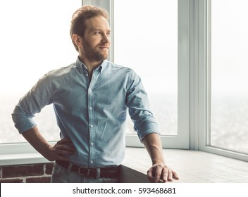 Handsome businessman is looking out the window and smiling while standing in office