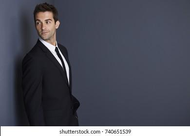 Handsome businessman looking over shoulder in studio