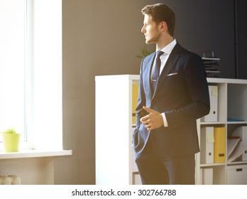 Handsome businessman looking through window