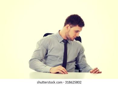 Handsome businessman looking under the desk.