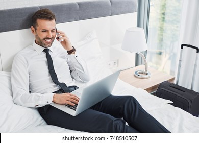 Handsome businessman making phonecall while sitting on hotel room bed and using laptop during business trip