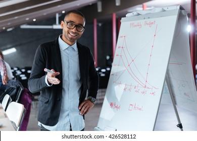 Handsome businessman making presentation using flipchart in the office