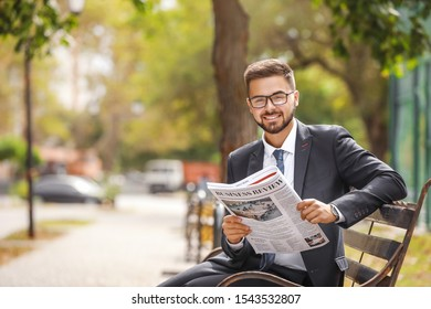 Handsome businessman with newspaper outdoors