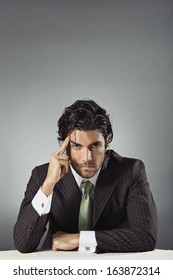Handsome businessman with pensive expression and copy space above head. Problem solving concept