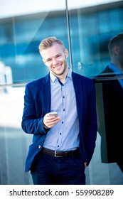 handsome businessman with phone smiling on a background of a glass building